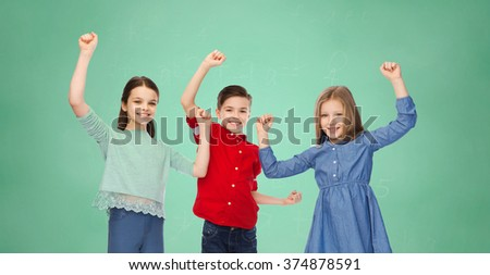 childhood, education, success, gesture and people concept - happy smiling boy and girls raising fists and celebrating victory over green school chalk board background - stock photo