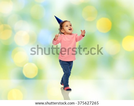 childhood, fashion, birthday, holidays and people concept - happy smiling african american little baby girl with birthday party hat catching something over green summer holidays lights background - stock photo