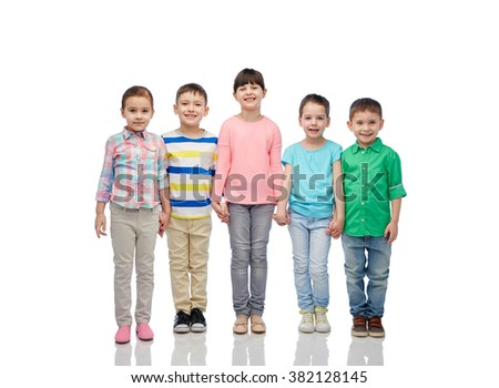 childhood, fashion, friendship and people concept - group of happy smiling little children holding hands - stock photo