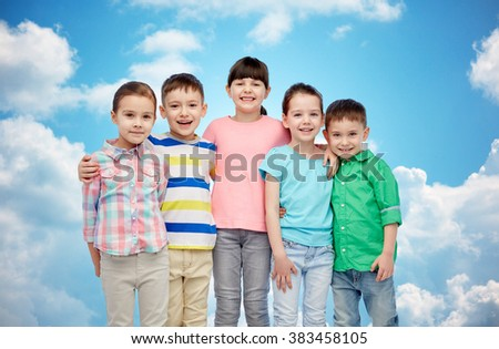 childhood, fashion, friendship and people concept - group of happy smiling little children hugging over blue sky and clouds background - stock photo
