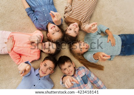 childhood, fashion, friendship and people concept - happy smiling children pointing finger to you and lying on floor in circle - stock photo