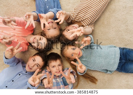 childhood, fashion, friendship and people concept - happy smiling children showing peace hand sign and lying on floorin circle - stock photo