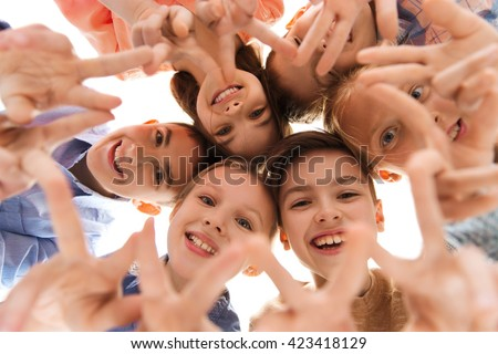childhood, fashion, friendship and people concept - happy smiling children showing peace hand sign and standing in circle - stock photo