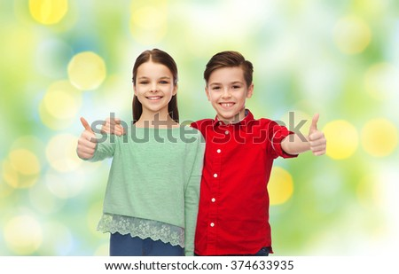 childhood, fashion, gesture and people concept - happy smiling boy and girl hugging and showing thumbs up over green lights background - stock photo