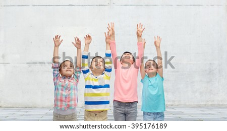 childhood, fashion, gesture and people concept - happy smiling children raising hands and celebrating victory over concrete wall on street background - stock photo