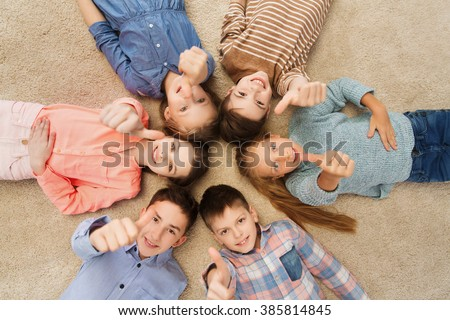 childhood, fashion, gesture and people concept - happy smiling children showing thumbs up and lying on floor in circle - stock photo