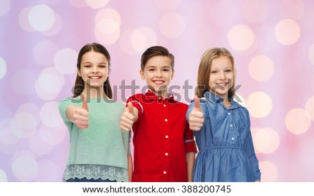 childhood, fashion, gesture and people concept - happy smiling children showing thumbs up over pink holidays lights background - stock photo