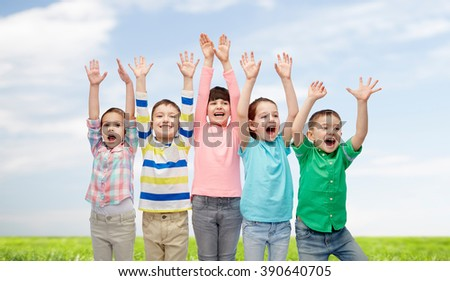 childhood, fashion, gesture and people concept - happy smiling friends raising fists and celebrating victory over blue sky and grass background