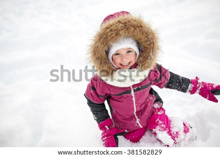childhood, fashion, season and people concept - happy little kid or girl in winter clothes playing with snow - stock photo