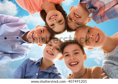 childhood, fashion, summer, friendship and people concept - happy smiling children faces over blue sky and clouds background - stock photo