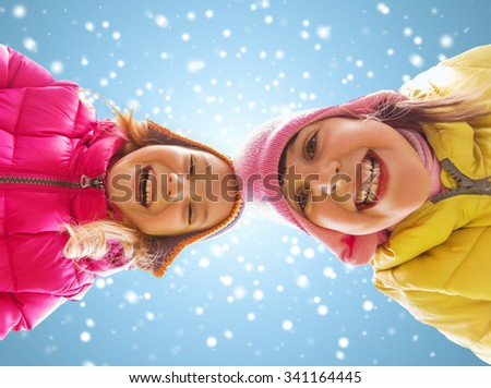 childhood, friendship, christmas, winter and people concept - happy little girls faces outdoors over blue sky and snow background - stock photo
