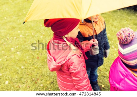 childhood, friendship, season, weather and people concept - close up of kids standing under umbrella in autumn park