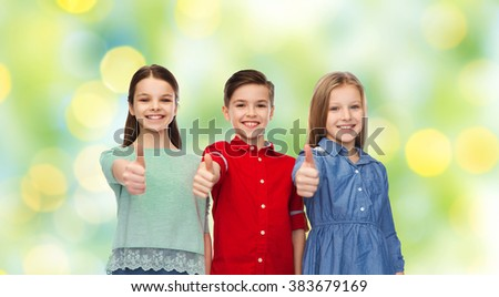 childhood, friendship, summer holidays, gesture and people concept - happy smiling children showing thumbs up over green lights background - stock photo
