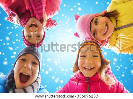 childhood, friendship, winter, christmas and people concept - happy little children faces outdoors over blue sky and snow background - stock photo