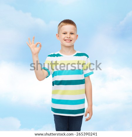 childhood, gesture and people concept - smiling little boy in casual clothes making ok gesture over cloudy background - stock photo