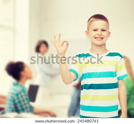 childhood, gesture, education and people concept - smiling little boy making ok gesture over group of students in classroom - stock photo
