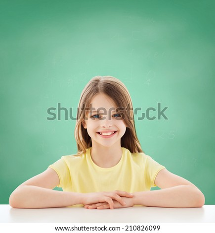 childhood, happiness, education, school and people concept - beautiful little girl sitting at table over green blackboard background - stock photo