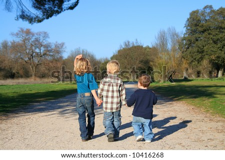 Childhood happiness. Three Kids Holding Hands in a nature reserve - stock photo