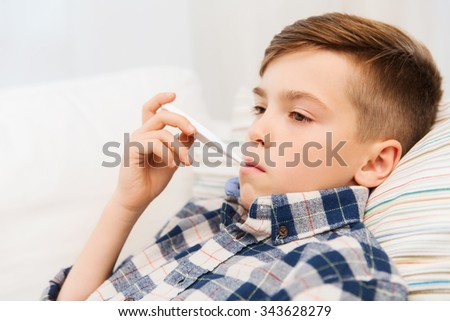 childhood, healthcare and medicine concept - ill boy with flu measuring temperature by thermometer at home - stock photo