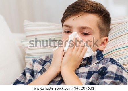 childhood, healthcare, rhinitis, people and medicine concept - ill boy with flu lying in bed and blowing his nose at home - stock photo