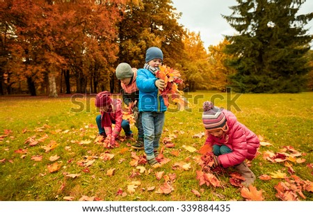 childhood, leisure, autumn, friendship and people concept - group of children collecting leaves in park - stock photo