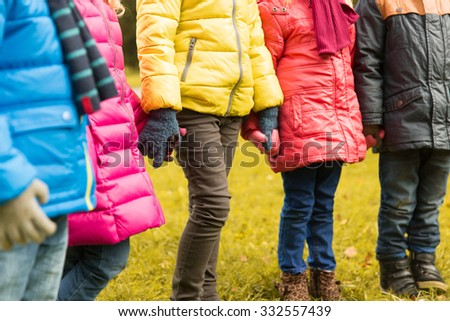 childhood, leisure, friendship and people concept - close up of happy children holding hands in autumn park - stock photo