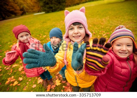 childhood, leisure, friendship and people concept - group of happy children waving hands in autumn park - stock photo