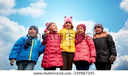 childhood, leisure, friendship and people concept - group of happy kids hugging over blue sky background
