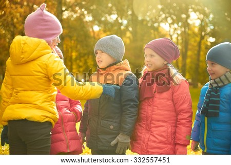 childhood, leisure, friendship and people concept - group of happy kids in autumn park counting and choosing game leader - stock photo
