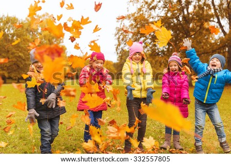 childhood, leisure, friendship and people concept - group of happy kids playing with autumn maple leaves and having fun in park - stock photo