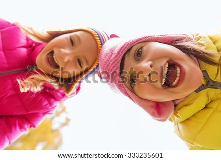 childhood, leisure, friendship and people concept - happy laughing girls faces outdoors - stock photo