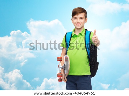 childhood, leisure, gesture, school and people concept - happy smiling student boy with backpack and skateboard showing thumbs up over blue sky and clouds background - stock photo