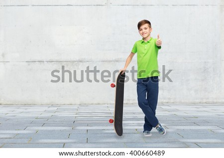 childhood, leisure, school and people concept - happy smiling boy with skateboard showing thumbs up over concrete gray wall on city street background - stock photo