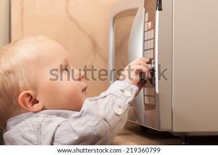 Childhood. Little boy child kid playing with timer of microwave oven kitchenware in the domestic kitchen at home. - stock photo