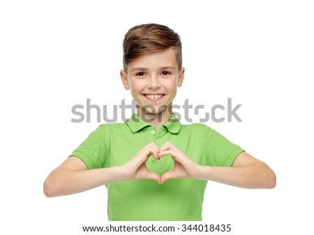 childhood, love, charity, health care and people concept - happy smiling boy in green polo t-shirt showing heart hand sign - stock photo
