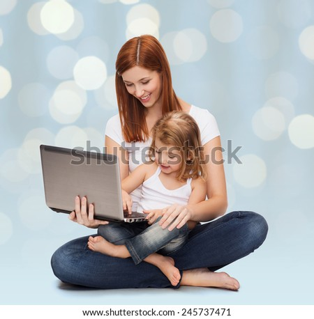 childhood, parenting and technology concept - happy mother with adorable little girl and laptop computer over holidays lights background - stock photo