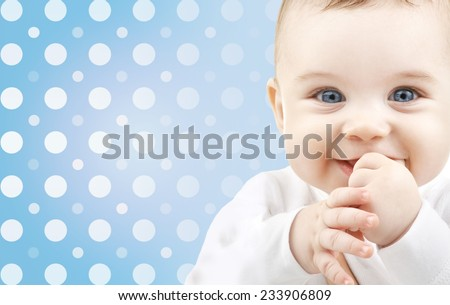 childhood, people and happiness concept - smiling baby boy face over blue and white polka dots pattern background - stock photo