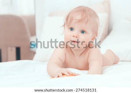 Childhood. Portrait of crawling baby boy on the bed curiously looking behind the camera