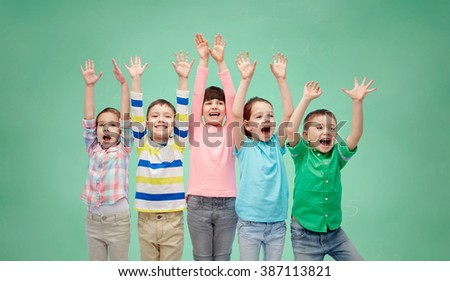 childhood, preschool education, gesture and people concept - happy smiling friends raising fists and celebrating victory over green school chalk board background - stock photo