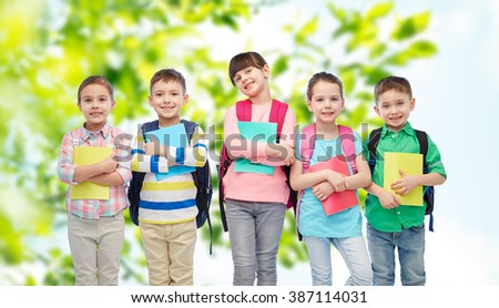 childhood, preschool education, learning and people concept - group of happy smiling little children with school bags and notebooks over summer green natural background - stock photo