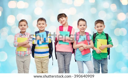 childhood, preschool education, learning and people concept - group of happy smiling little children with school bags and notebooks over blue holidays lights background - stock photo