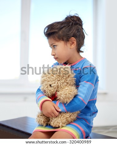 childhood, sadness, loneliness and people concept - sad little girl with teddy bear toy at home - stock photo