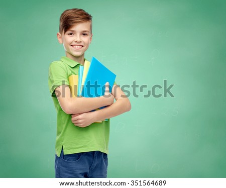 childhood, school, education and people concept - happy smiling student boy with folders and notebooks over green school chalk board background - stock photo