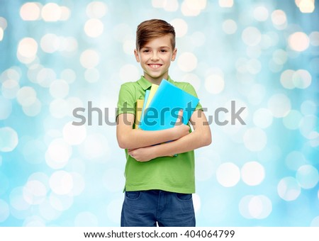 childhood, school, education and people concept - happy smiling student boy with folders and notebooks over blue holidays lights background - stock photo