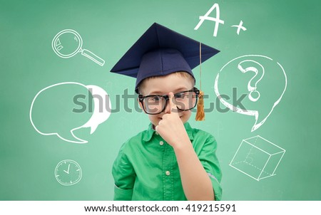 childhood, school, education, knowledge and people concept - happy boy in bachelor hat or mortarboard and eyeglasses over doodles on green chalk board background - stock photo