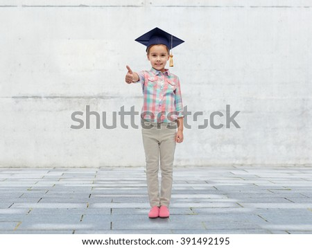 childhood, school, education, learning and people concept - happy girl with in bachelor hat or mortarboard showing thumbs up over urban concrete background - stock photo