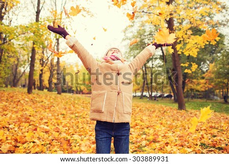 childhood, season and people concept - smiling little girl having fun in autumn park - stock photo