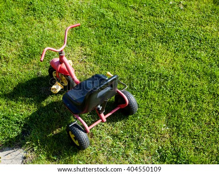 Childhood. Small red tricycle cycle toy on the green grass. Outdoor. Play and learn.