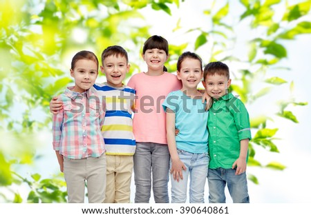childhood, summer, fashion, friendship and people concept - group of happy smiling little children hugging over green natural background - stock photo