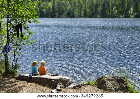 Childhood - the children are sitting on the bank of the river